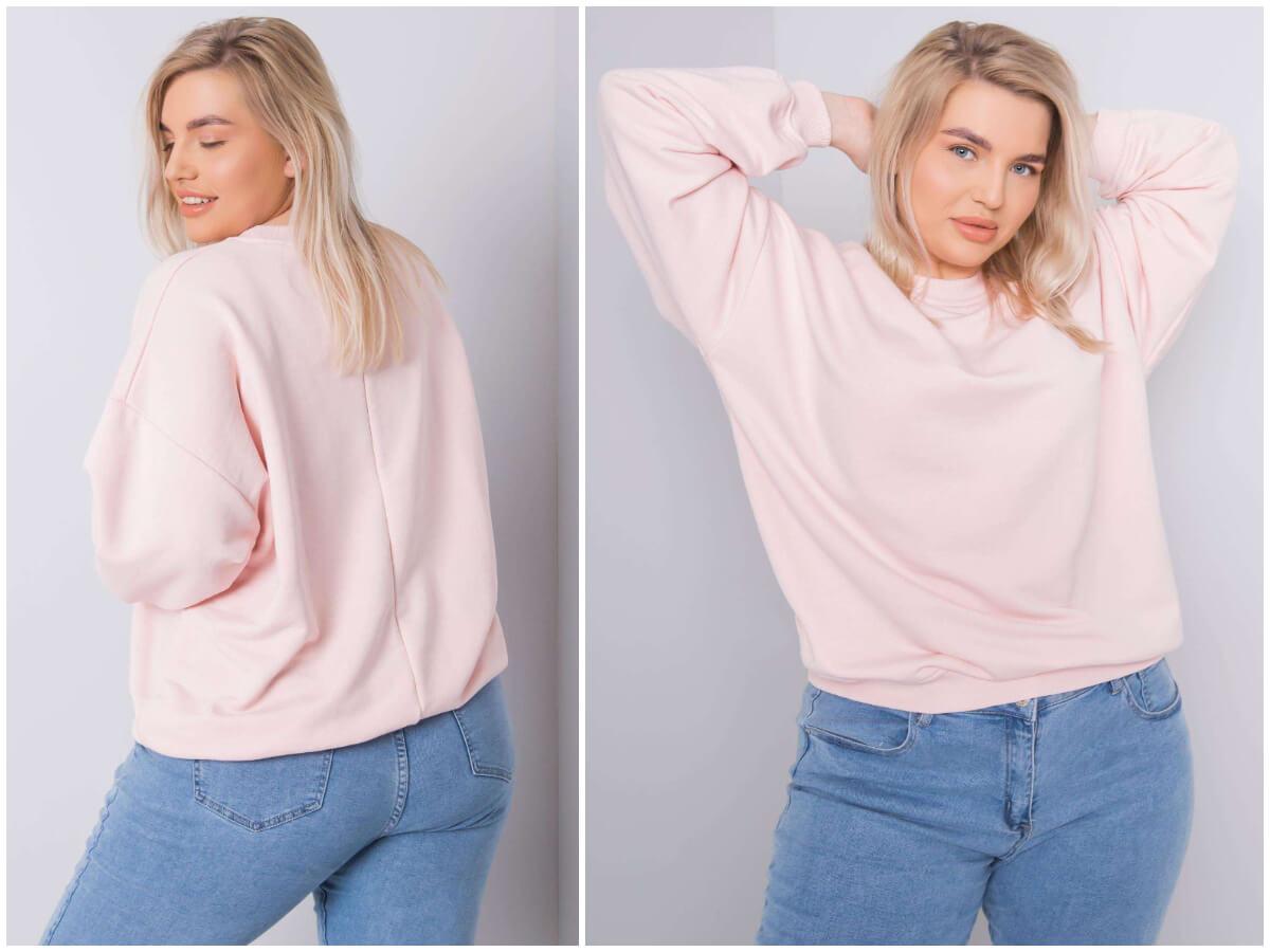 Modelka plus size pozuje do zdjęć ubrana w jasnoróżową bluzę