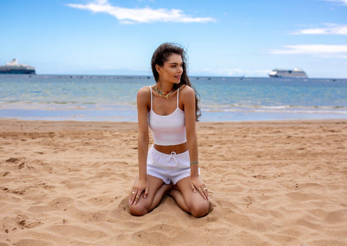 Modelka ubrana w komplet na lato klęczy na plaży, uśmiecha się i patrzy w lewą stronę. W tle morze i okręty.