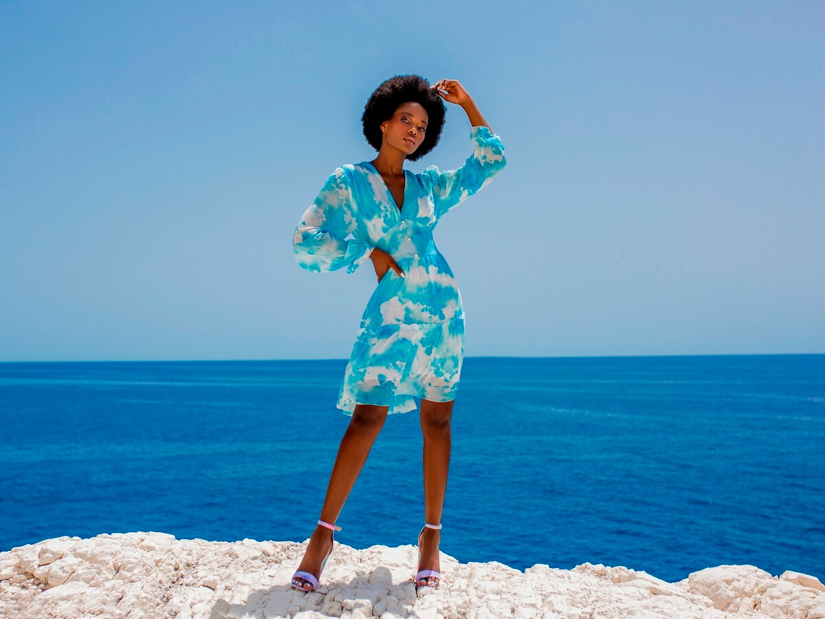 Modelka stoi na skale na tle morza i promuje kolor niebieski w stylizacjach