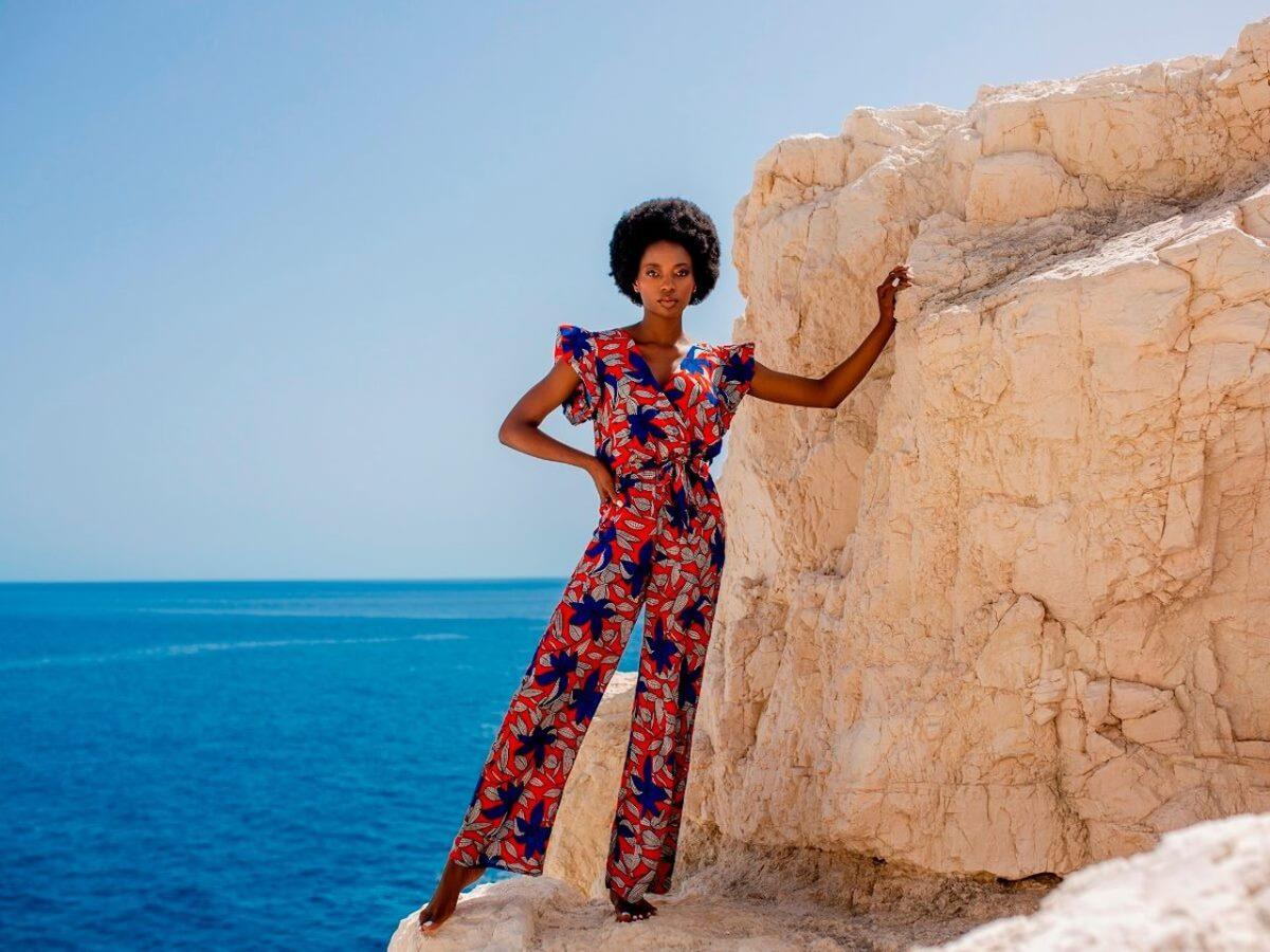 Kobieta w kombinezonie stoi na skale na tle morza. Promuje tekst o 5 rodzajach sylwetek damskich.