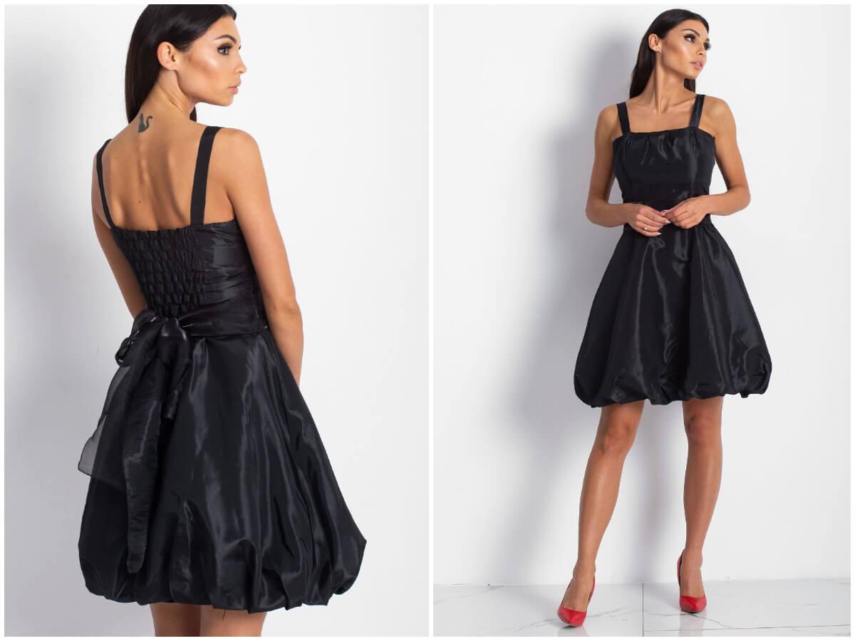 Czarna satynowa sukienka na wesele w stylizacji na modelce. Tło gładkie.
